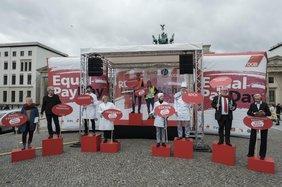 Berufspaare vor Brandenburger Tor, die mit Schildern auf Lohnlücke hinweisen