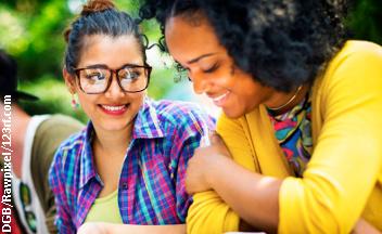 Zwei Studentinnen sitzen nebeneinander am Tisch