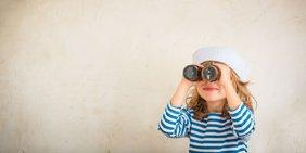 Kleines Mädchen schaut durch ein Fernglas