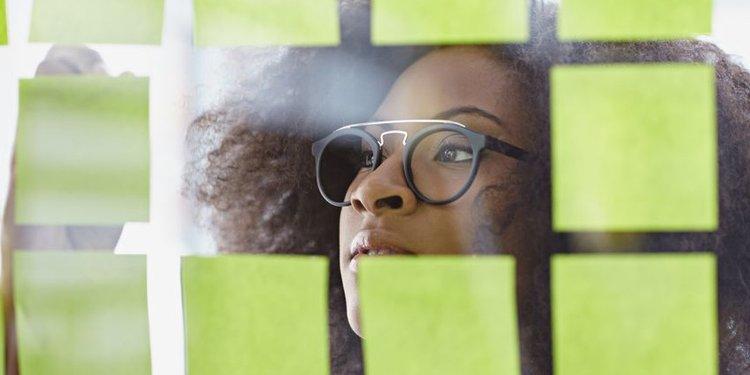 Junge Frau schaut auf Glaswand mit Klebezetteln