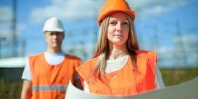 Frau in Schutzkleidung hält Plan in den Händen