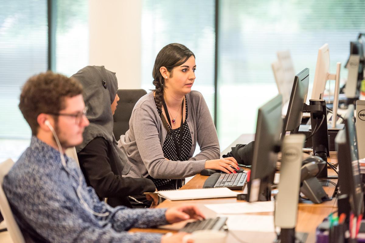 drei (junge) Menschen im Büro, vor PC