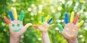 Drei Hände bunt bemalt strecken sich in die Luft