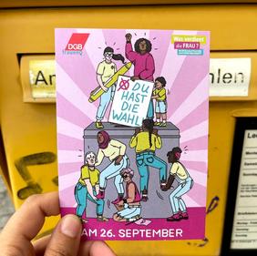 Postkarte wird vor Briefkasten gehalten