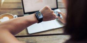 Frau am Laptop schaut auf Armbanduhr