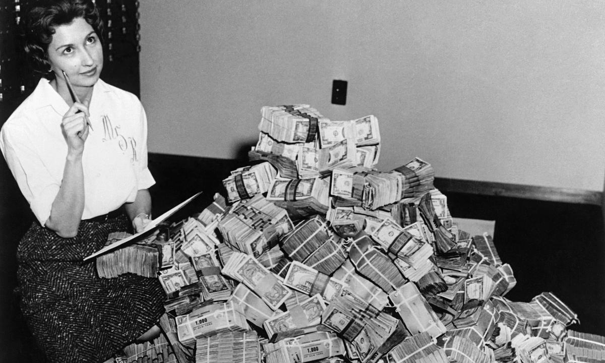 Schwarz-weiß Bild einer Frau, die neben einem Berg Geldscheine sitzt und freundlich-nachdenklich aussieht