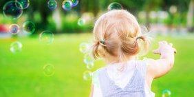 Kleines Mädchen mit Seifenblasen auf Wiese